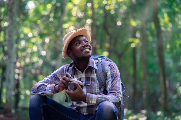 Viajero africano del hombre de la libertad que sostiene la cámara con la mochila en el bosque natural verde.