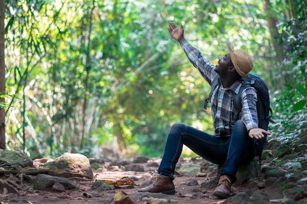 Viajero africano del hombre de la libertad que sostiene la cámara con la mochila que se coloca en el bosque natural verde.