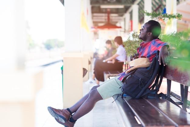 Viajero africano del hombre que se sienta con el teléfono que espera del teléfono inteligente, de la cámara y del bolso para en la estación de tren