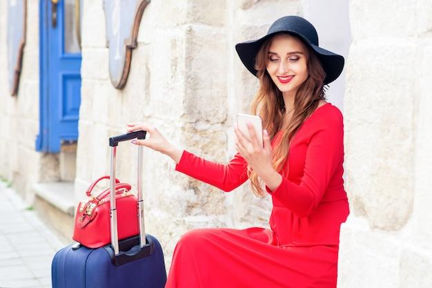 Viajero agradable mujer está buscando en el teléfono inteligente en la calle.