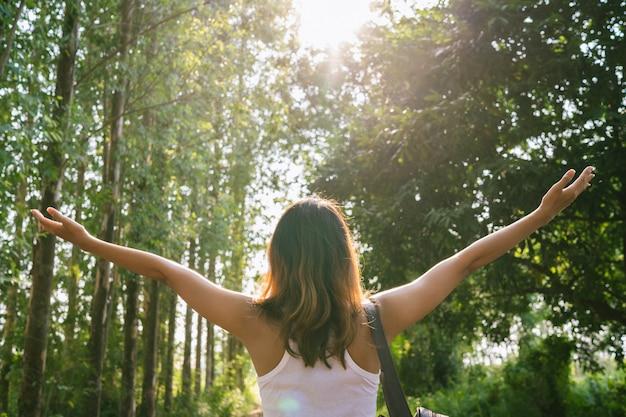 Viajero asiático joven feliz de la mujer con la mochila que camina en bosque.