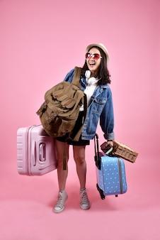 El viajero asiático sonriente de la mujer lleva mucho equipaje