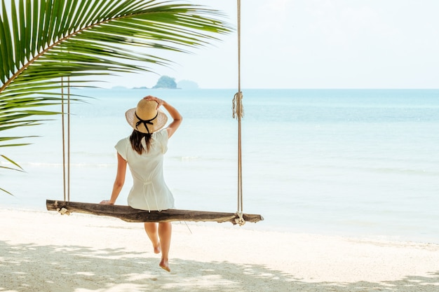 Viajero atractivo mujer sentada en un columpio en la playa