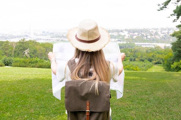 Viajero desde atrás está mirando el mapa