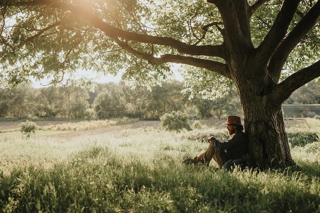 Viajero barbudo sentado bajo un árbol y descansando