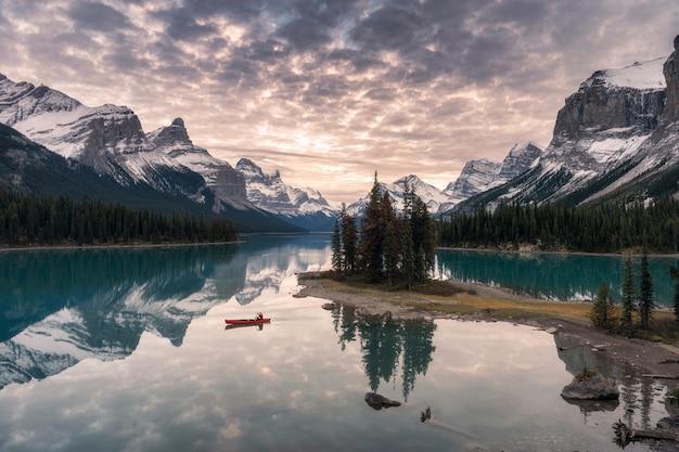 Viajero en canoa con reflejo de montaña rocosa en el lago maligne en la isla spirit en el parque nacional jasper