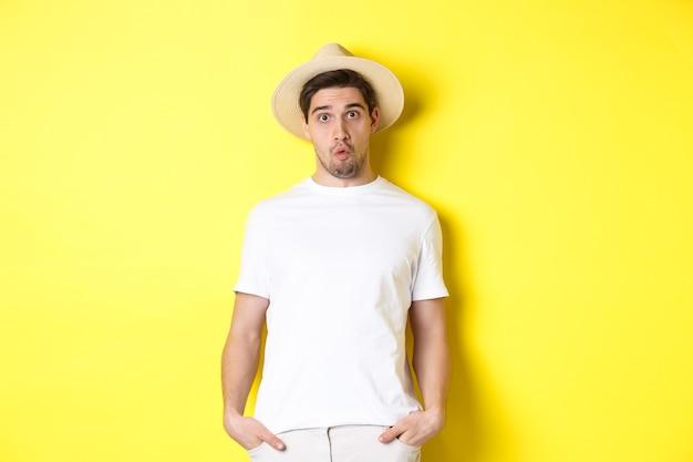 Viajero chico confundido con sombrero de paja mirando desconcertado, mirar fijamente a la cámara, de pie sobre fondo amarillo. copia espacio