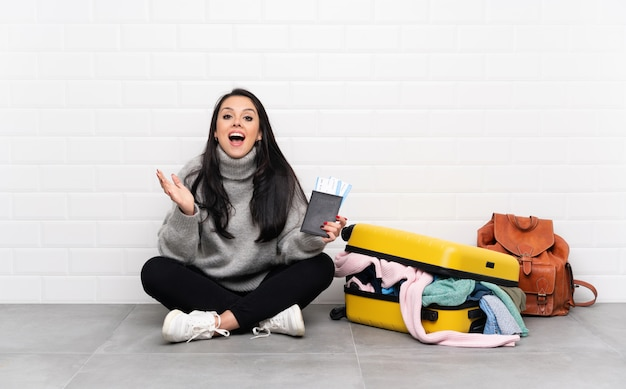 Viajero colombiana con una maleta llena de ropa sentada en el suelo infeliz y frustrada con algo