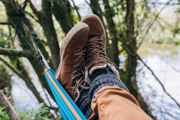 Viajero de cultivos irreconocible en botas de trekking relajándose en una hamaca entre árboles mientras disfruta del fin de semana cerca del río en el bosque