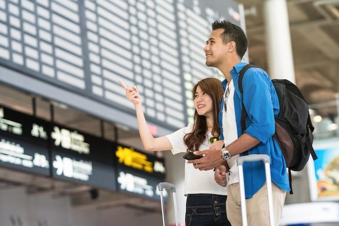 Viajero de pareja asiática sosteniendo el teléfono móvil inteligente
