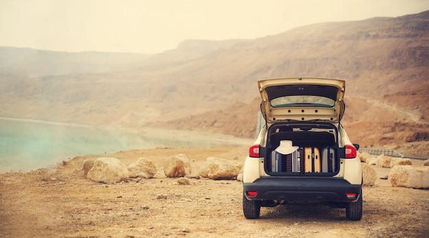 Viajero elegante feliz de la mujer joven en el camino de la playa que se sienta en el coche blanco de la cruce