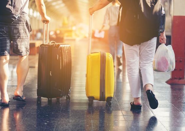 Viajero con equipaje en la pasarela en la estación de tren