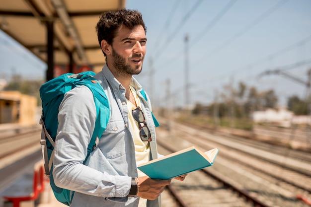 Viajero esperando el tren en la plataforma de la estación