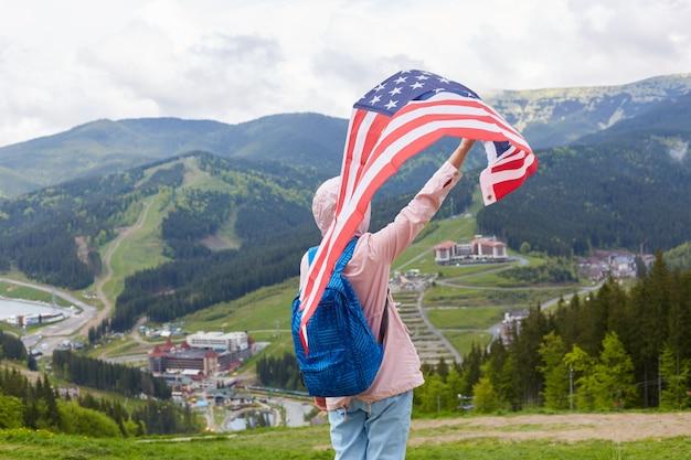 Viajero experimentado con jeans, chaqueta rosa con capucha y mochila azul, levantando una gran bandera de ee. uu., sensación de libertad, recorrido turístico