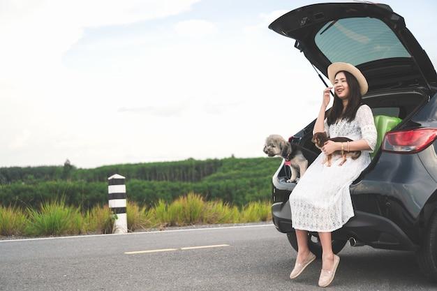 Viajero feliz de la mujer joven que se sienta en coche con los perros en el camino y el cielo de la puesta del sol.