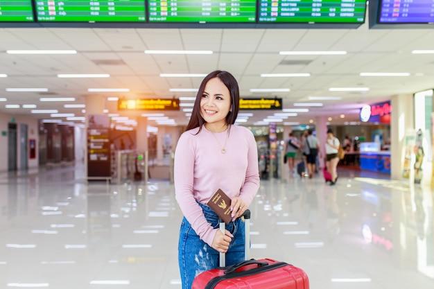 Viajero femenino asiático que comprueba el tablero de las salidas del vuelo.