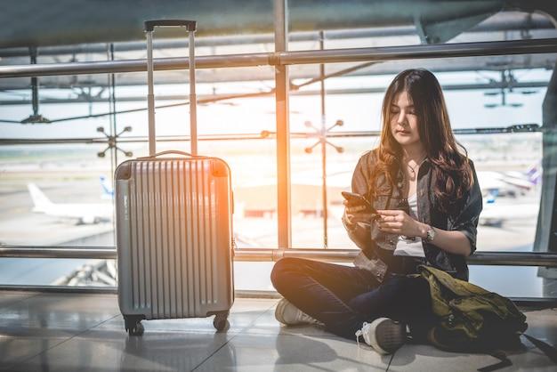 Viajero femenino asiático que usa el teléfono inteligente para verificar el horario de vuelo en el aeropuerto