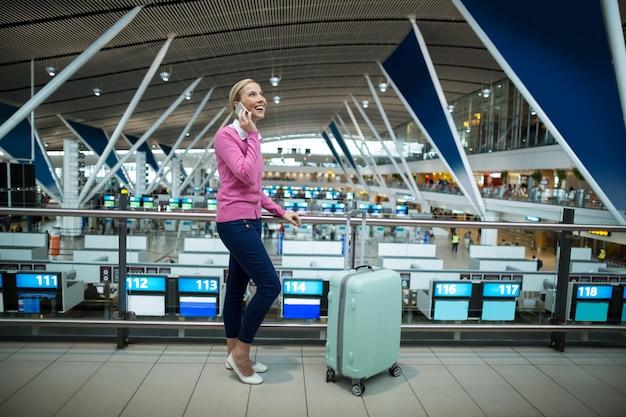 Viajero femenino con equipaje hablando por teléfono móvil