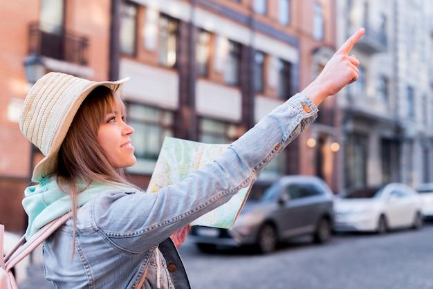 Viajero femenino feliz que sostiene el mapa en la mano que señala en algo en la ciudad