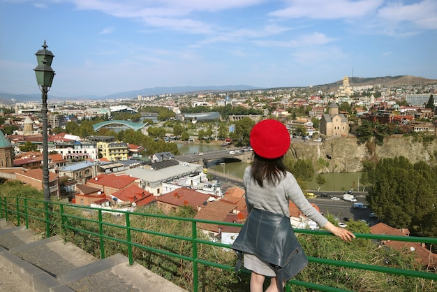 Viajero femenino impresionado por la vista panorámica con muchos de los monumentos de tbilisi, georgia