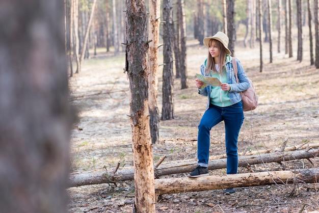 Viajero femenino joven que camina en el bosque que sostiene el mapa disponible