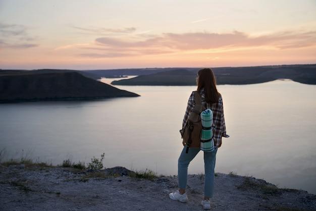 Viajero femenino con mochila de pie en la colina en la bahía de bakota