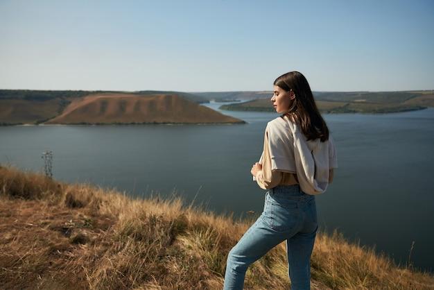 Viajero femenino de pie sobre el borde de la roca en la bahía de bakota