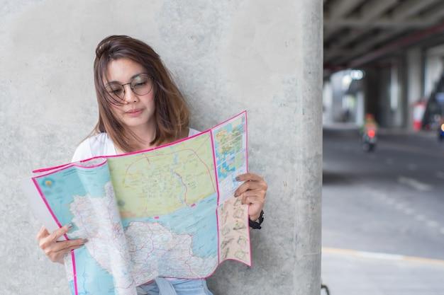 Viajero femenino que busca un mapa para viajar en la ciudad