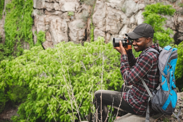 Viajero hombre africano sentado en el acantilado y sosteniendo la cámara con mochila