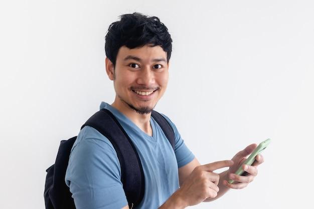 Viajero hombre asiático con una mochila está utilizando una aplicación de teléfono móvil.