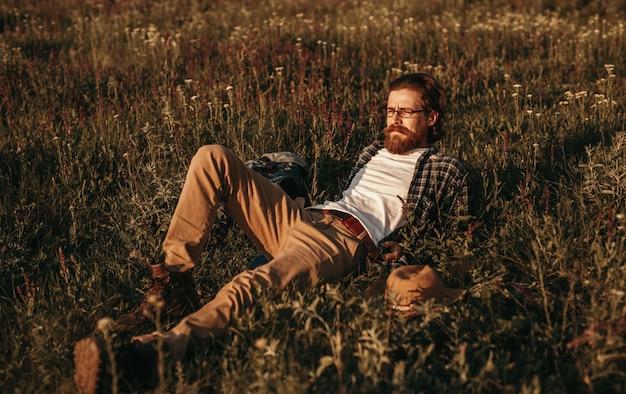 Viajero hombre barbudo tumbado en el campo y mirando lejos