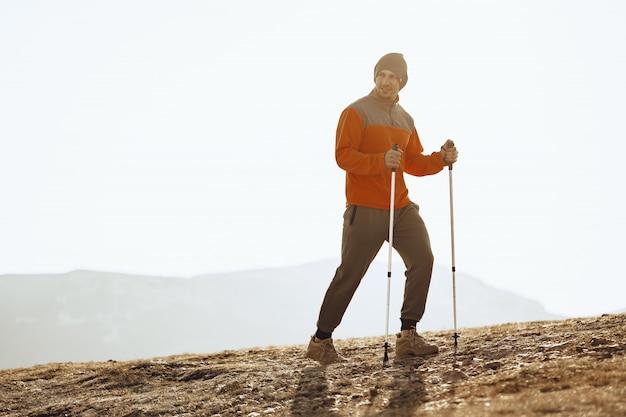 Viajero hombre con bastones de trekking subiendo la montaña