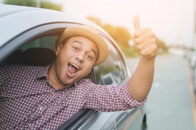Viajero de hombre en la carretera. dentro del coche mostrando el pulgar hacia arriba al aire libre. listo para salir.