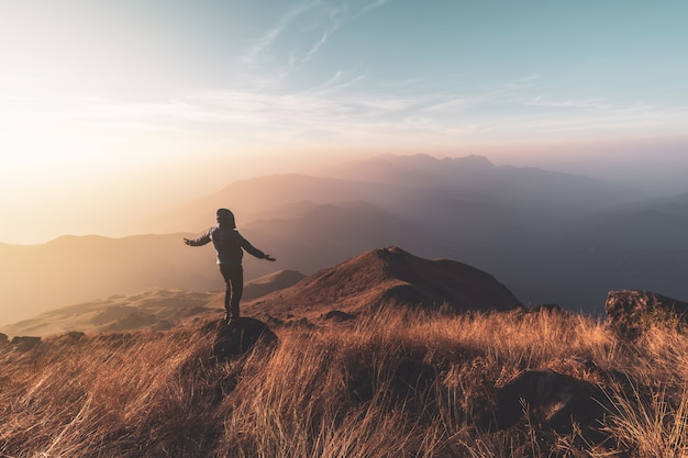 Viajero del hombre joven que mira paisaje hermoso en la puesta del sol en la montaña