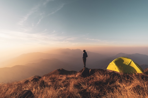 Viajero del hombre joven que mira paisaje en la puesta del sol y que acampa en la montaña