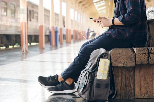 El viajero del hombre joven que se sienta con el uso del teléfono móvil elige adónde viajar y bolso que espera el tren en la estación de tren. backpacker en la estación de tren y que mira en el teléfono móvil el plan para viajar.