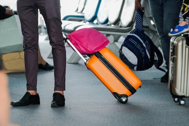 Viajero hombre con maleta de viaje o equipaje caminando en la pasarela de la terminal del aeropuerto