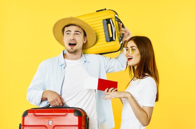 Viajero de hombre y mujer con una maleta, fondo de color, alegría, pasaporte
