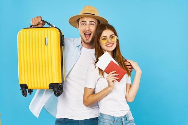 Viajero de hombre y mujer con una maleta, superficie coloreada, alegría, pasaporte