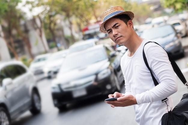 Viajero infeliz, treveller con aplicación de teléfono inteligente en atascos de tráfico pesado