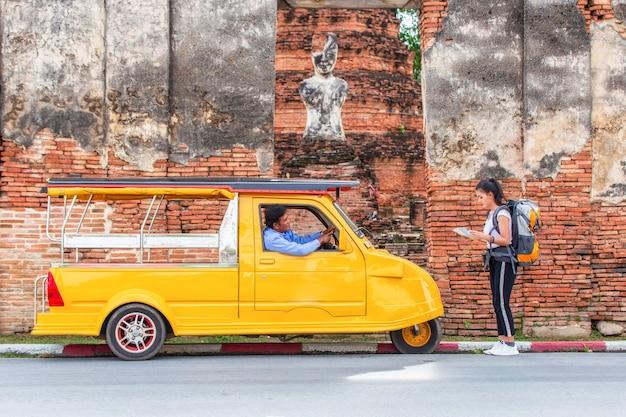 Viajero japonés chica hollding mapa viaje consulta para el camino con viejo conductor taxi o tuk tuk gira.