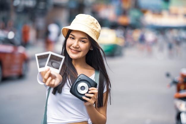 Viajero joven asiática mochila mujer con sombrero caminando en khao san road manos sosteniendo cámara instantánea y película para tomar una foto, famoso monumento itinerante en la ciudad de bangkok de tailandia.