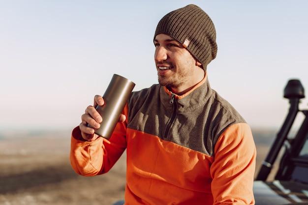 Viajero joven bebiendo de su termocup mientras se detiene en una caminata, retrato de primer plano