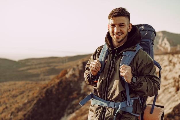Viajero joven caucásico con mochila grande senderismo en las montañas