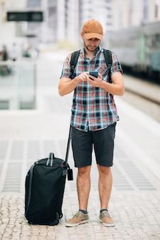 Viajero joven en la estación de ferrocarril con teléfono en la estación de tren