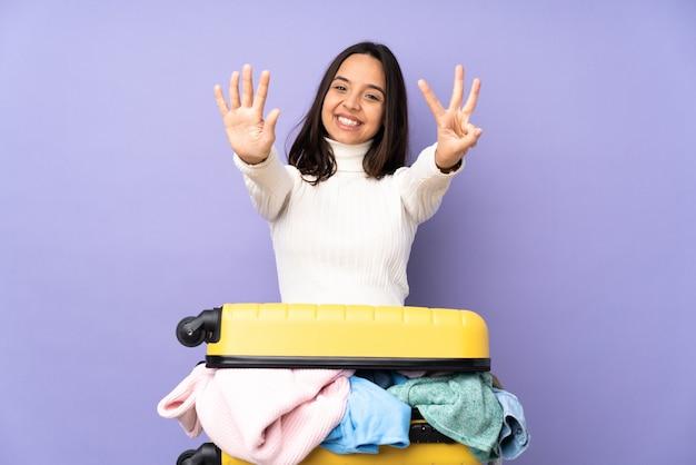 Viajero joven con una maleta llena de ropa en púrpura aislado contando ocho con los dedos