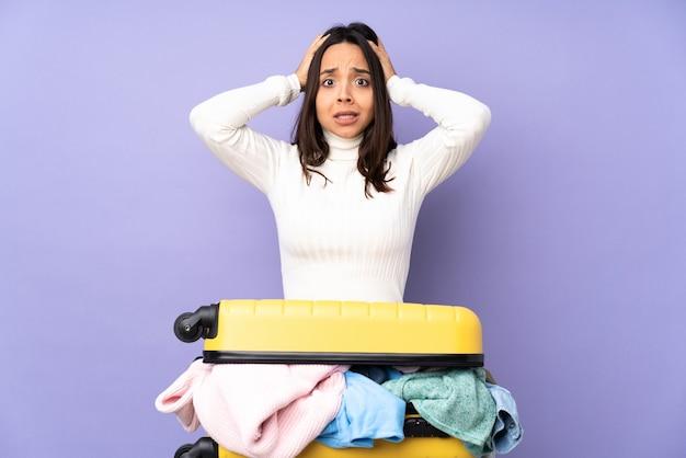 Viajero joven con una maleta llena de ropa en púrpura aislado frustrado y toma las manos en la cabeza