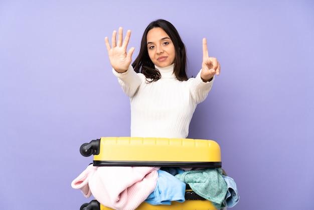Viajero joven con una maleta llena de ropa sobre fondo púrpura aislado contando seis con los dedos