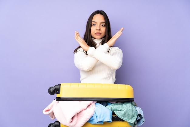 Viajero joven con una maleta llena de ropa sobre fondo púrpura aislado sin hacer ningún gesto