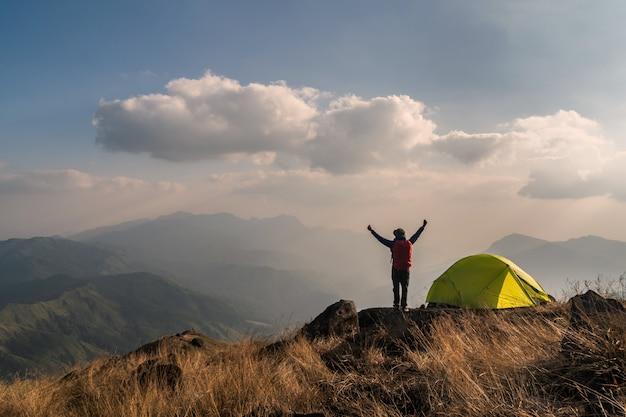 Viajero joven con mochila acampando en montaña